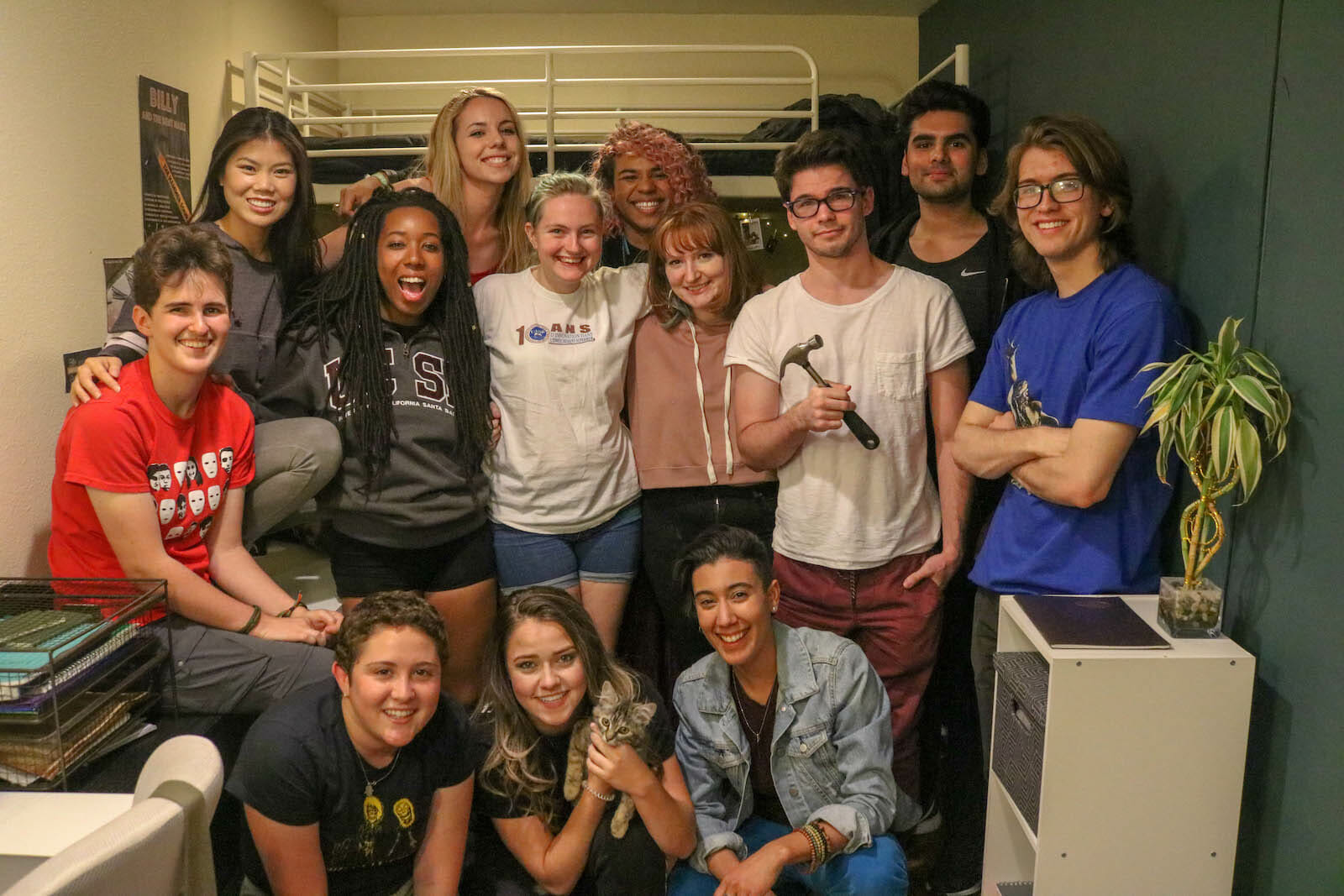 "Cast and crew photo on the last full-cast day of shooting on set. Top row from left: Ana Ming Bostwick-Singer, Meredith ""Kat"" Wells, Justice Schiappa, Arjun Sarup. Middle row from left: Ursula Collins-Laine, Joré Aaron, Christa Troester, Emma Drewry, Jay Borgwardt, Isaac Sanchez. Bottom row from left: Miriam Sachs, KatieMichal Pullen (holding a kitten named April), Victoria Ortiz. Photographed by Miriam Sachs."