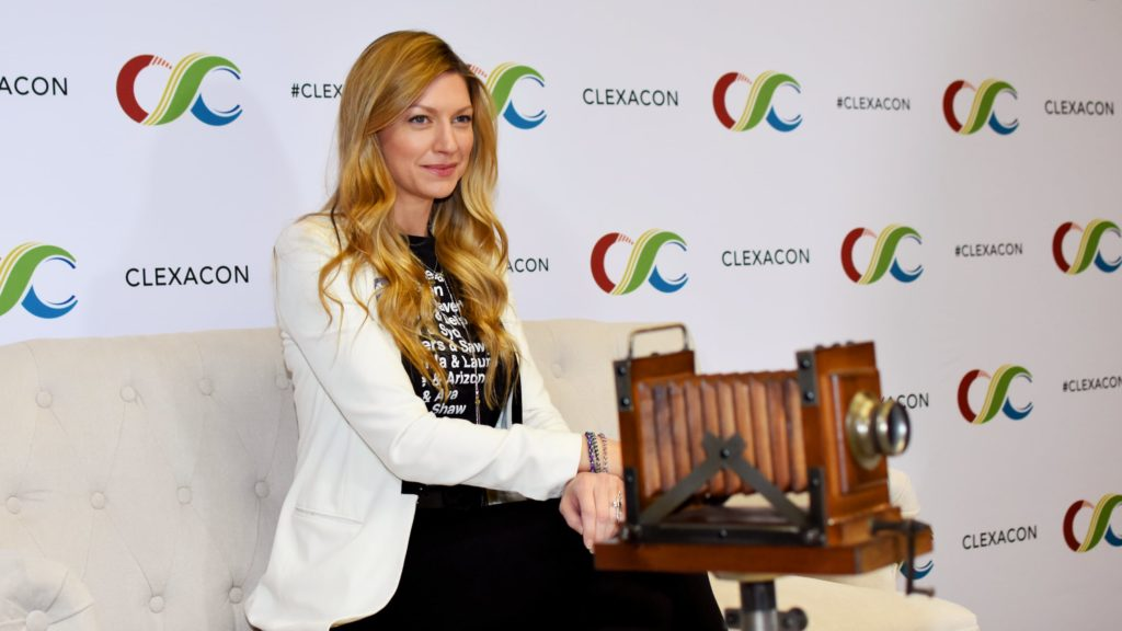 Jes Macallan sitting on a couch, smiling. (Photo by Mika Epstein/LezWatch.TV)