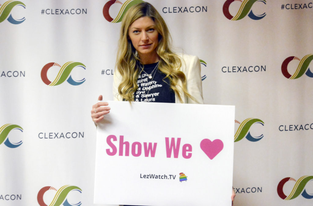 Jes Macallan with the LezWatchTV Show We Love sign