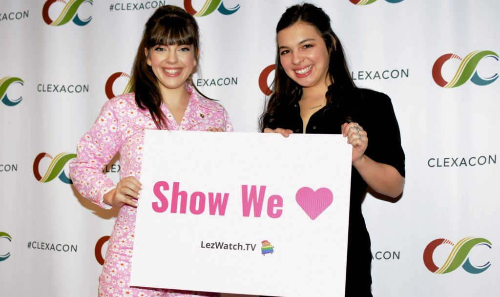 "Sheridan Pierce and Isabella Gomez holding a sign that says ""Show We Love"" - LezWatch.TV  (Photo by Tracy Levesque/LezWatch.TV)"