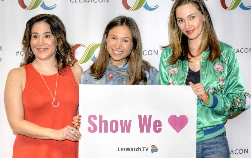 "Emily Andras, Dominique Provost-Chalkley and Katherine Barrell holding a sign that says ""Show We Love - LezWatch.TV"" (Photo by Tracy Levesque/LezWatch.TV)"