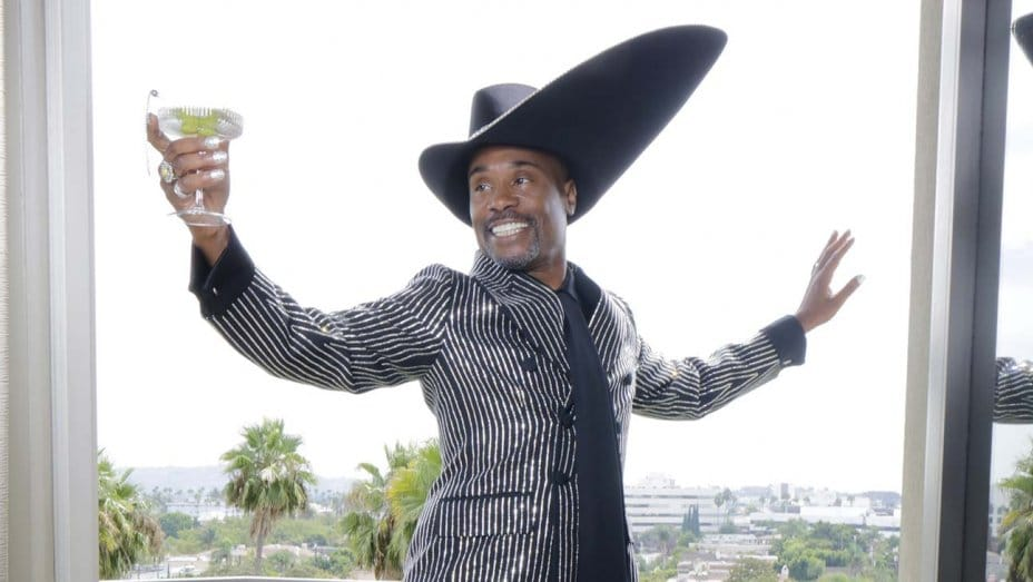 Billy Porter holding up a drink and looking fabulous.